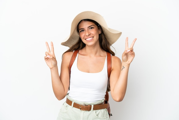 Jonge kaukasische vrouw die een pamela draagt in de zomervakantie die op witte achtergrond wordt geïsoleerd die overwinningsteken met beide handen toont