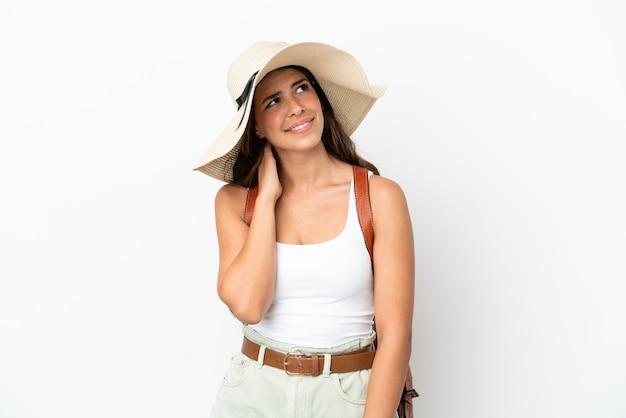 Jonge kaukasische vrouw die een pamela draagt in de zomervakantie die op witte achtergrond wordt geïsoleerd en een idee denkt