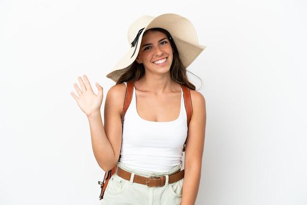 Jonge kaukasische vrouw die een pamela draagt in de zomervakantie die op witte achtergrond wordt geïsoleerd en met de hand salueert met een gelukkige uitdrukking