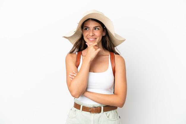 Jonge kaukasische vrouw die een pamela draagt in de zomervakantie die op witte achtergrond wordt geïsoleerd en naar de zijkant kijkt