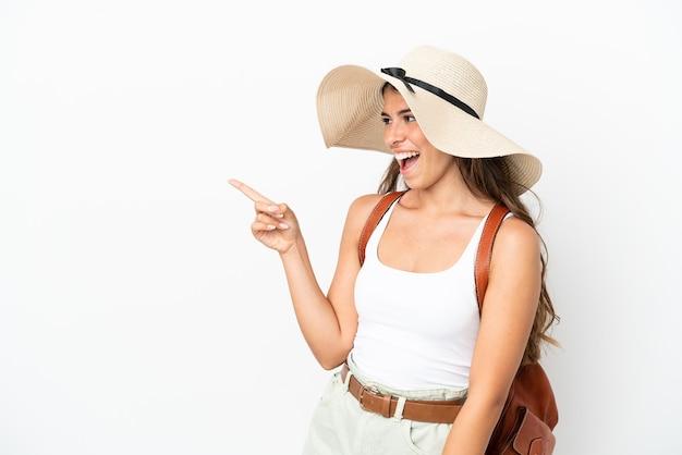 Jonge kaukasische vrouw die een pamela draagt in de zomervakantie geïsoleerd op een witte achtergrond die met de vinger naar de zijkant wijst en een product presenteert