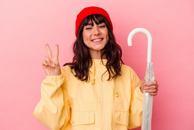 Jonge kaukasische vrouw die een paraplu houdt die op roze achtergrond wordt geïsoleerd die nummer twee met vingers toont.