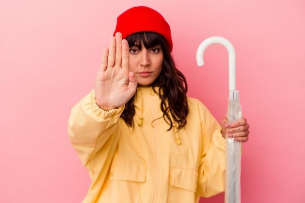 Jonge kaukasische vrouw die een paraplu houdt die op roze achtergrond wordt geïsoleerd die zich met uitgestrekte hand bevindt die stopbord toont, dat u verhindert.