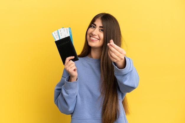 Jonge kaukasische vrouw die een paspoort houdt dat op gele achtergrond wordt geïsoleerd die geldgebaar maakt
