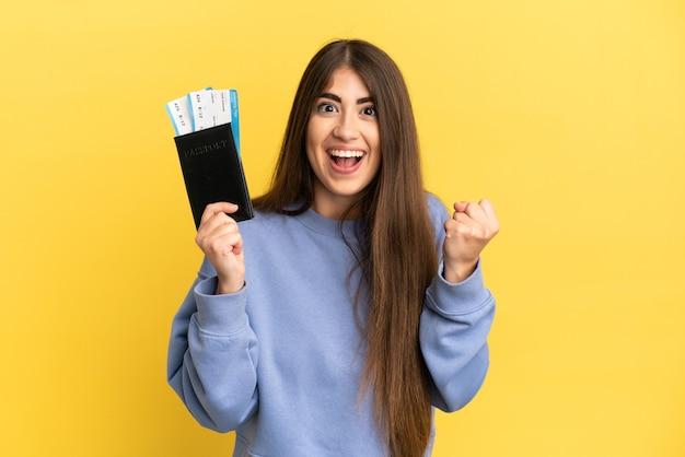 Jonge kaukasische vrouw die een paspoort houdt dat op gele achtergrond wordt geïsoleerd en een overwinning in winnaarpositie viert