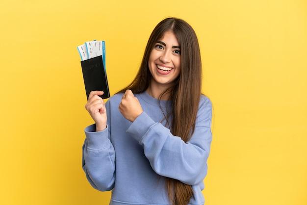 Jonge kaukasische vrouw die een paspoort houdt dat op gele achtergrond wordt geïsoleerd en een overwinning viert