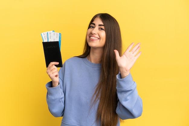 Jonge kaukasische vrouw die een paspoort houdt dat op gele achtergrond wordt geïsoleerd en met de hand salueert met een gelukkige uitdrukking