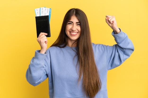 Jonge kaukasische vrouw die een paspoort houdt dat op gele achtergrond wordt geïsoleerd en sterk gebaar doet