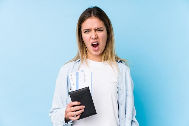 Jonge kaukasische vrouw die een paspoort houdt dat zeer boos en agressief gilt.