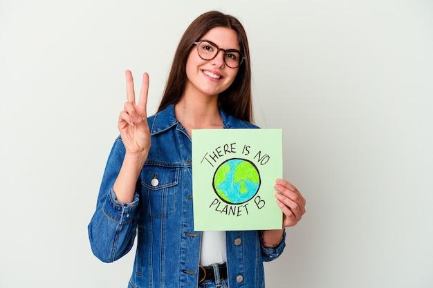 Jonge kaukasische vrouw die een plakkaat van het veganistleven houdt dat op witte achtergrond wordt geïsoleerd en erg boos en agressief schreeuwt.