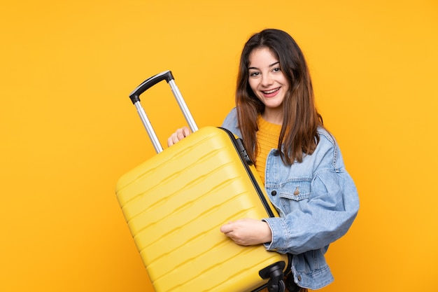 Jonge kaukasische vrouw die een reiskoffer houdt