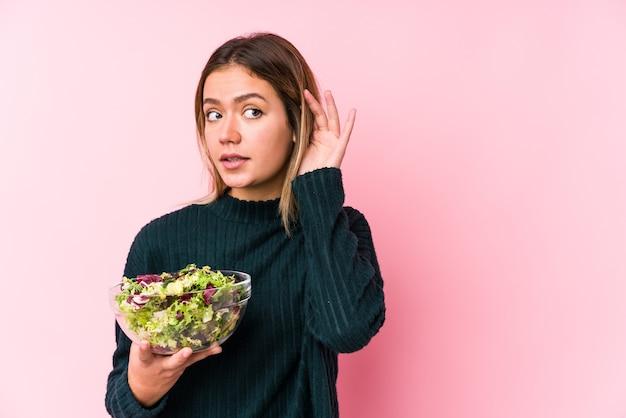 Jonge kaukasische vrouw die een salade houdt die een roddel probeert te luisteren.