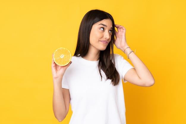 Jonge kaukasische vrouw die een sinaasappel op gele muur houdt die twijfels en met verwarde gezichtsuitdrukking heeft