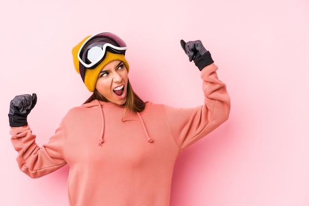 Jonge kaukasische vrouw die een ski draagt ?? geïsoleerde het opheffen vuist na een overwinning, winnaarconcept.