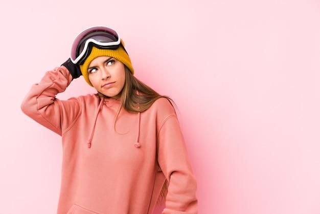 Jonge kaukasische vrouw die een skikleren draagt geïsoleerd die achterkant van het hoofd raakt, denkt en een keus maakt.