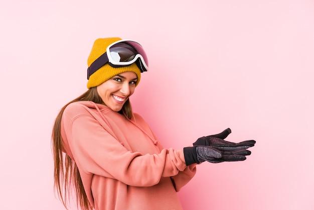 Jonge kaukasische vrouw die een skikleren draagt geïsoleerd die een exemplaarruimte op een palm houdt.