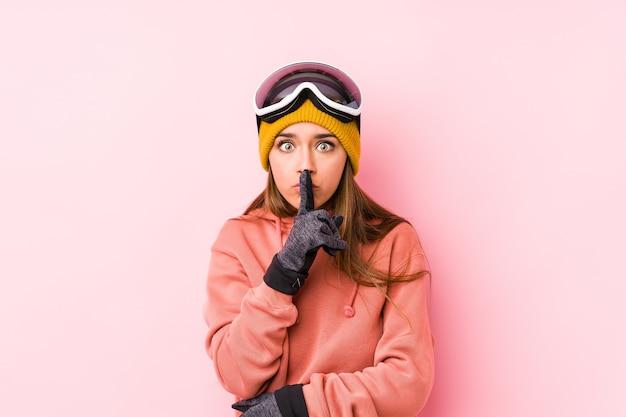 Jonge kaukasische vrouw die een skikleren draagt geïsoleerd die een geheim houdt of om stilte vraagt.