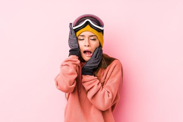 Jonge kaukasische vrouw die een skikleren draagt geïsoleerd mankerend en troosteloos huilen.