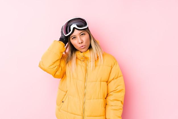 Jonge kaukasische vrouw die een skikleren in een roze muur draagt, moe en erg slaperig hand op het hoofd houden.