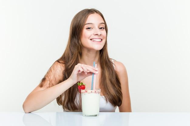 Jonge kaukasische vrouw die een smoothie drinkt