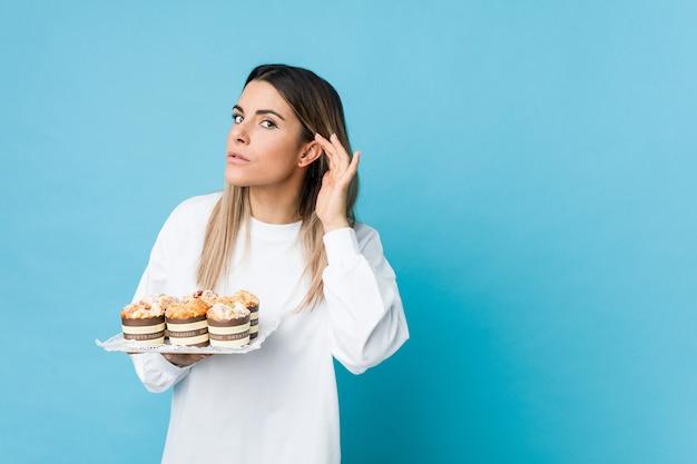 Jonge kaukasische vrouw die een snoepjescake houdt die aan een roddel proberen te luisteren.