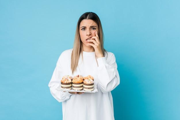 Jonge kaukasische vrouw die een snoepjescake houdt die nagels bijt, zenuwachtig en zeer bezorgd.