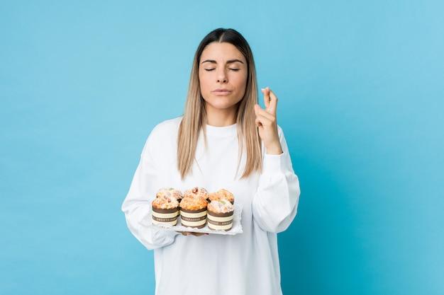 Jonge kaukasische vrouw die een snoepjescake houdt die vingers kruist voor het hebben van geluk