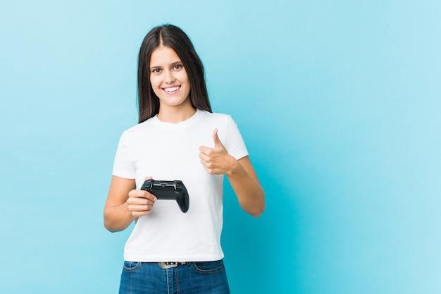 Jonge kaukasische vrouw die een spelcontrolemechanisme houdt dat en duim glimlacht opheft