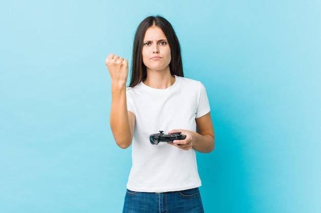 Jonge kaukasische vrouw die een spelcontrolemechanisme houdt dat vuist toont aan camera, agressieve gelaatsuitdrukking.