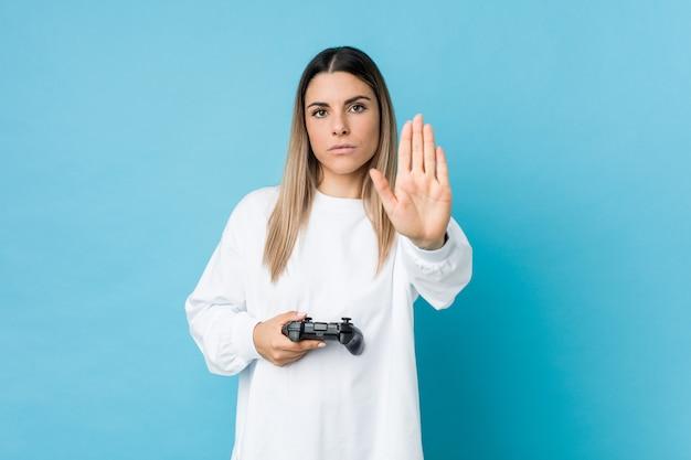 Jonge kaukasische vrouw die een spelcontrolemechanisme houdt die zich met uitgestrekte hand bevindt die eindeteken toont, dat u verhindert.