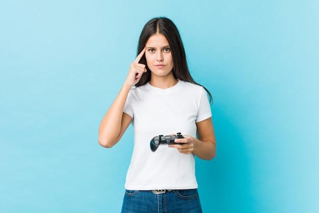 Jonge kaukasische vrouw die een spelcontrolemechanisme houdt die zijn tempel met vinger richt, het denken, concentreerde zich op een taak.
