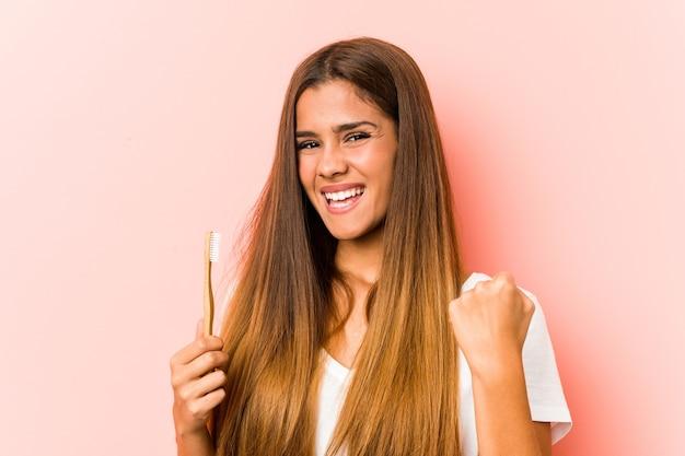 Jonge kaukasische vrouw die een tandenborstel houdt die zorgeloos en opgewonden juicht.