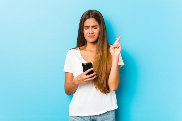 Jonge kaukasische vrouw die een telefoon houdt die vingers kruist voor het hebben van geluk