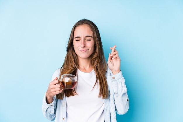 Jonge kaukasische vrouw die een thee houdt die vingers kruist voor het hebben van geluk