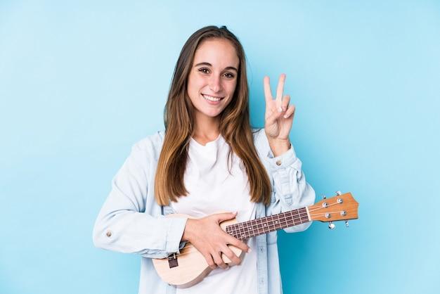 Jonge kaukasische vrouw die een ukelele geïsoleerd houdt die nummer twee met vingers toont.