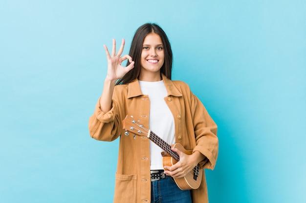 Jonge kaukasische vrouw die een ukelele vrolijk en zeker houdt die ok gebaar toont.