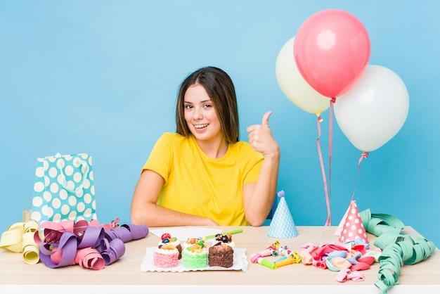 Jonge kaukasische vrouw die een verjaardag organiseert die en duim glimlacht opheft
