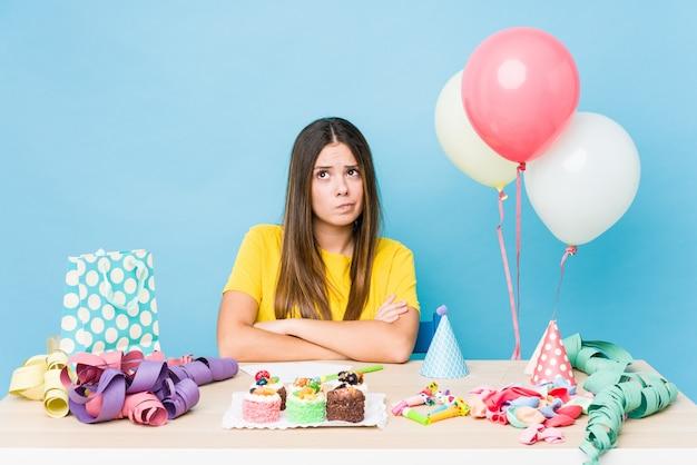 Jonge kaukasische vrouw die een verjaardag organiseert die ongelukkig met sarcastische uitdrukking kijkt.