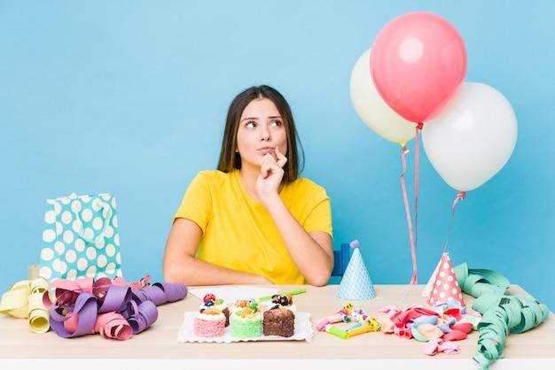 Jonge kaukasische vrouw die een verjaardag organiseert die zijdelings met twijfelachtige en sceptische uitdrukking kijkt.