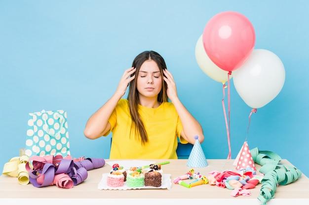 Jonge kaukasische vrouw die een verjaardag organiseert en hoofdpijn heeft.