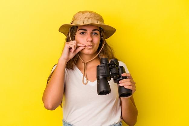 Jonge kaukasische vrouw die een verrekijker houdt die op gele achtergrond met vingers op lippen wordt geïsoleerd die een geheim houden.