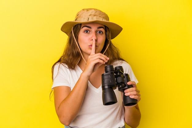 Jonge kaukasische vrouw die een verrekijker houdt die op gele achtergrond wordt geïsoleerd die een geheim houdt of om stilte vraagt.