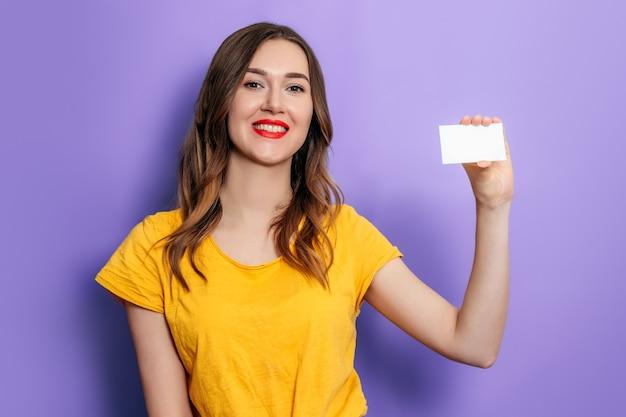 Jonge kaukasische vrouw die een visitekaartje in haar hand houdt en glimlacht, geel t-shirt draagt op een lila achtergrond in de studio. krediet online. mockup