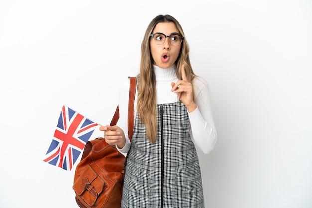 Jonge kaukasische vrouw die een vlag van het verenigd koninkrijk houdt die op witte achtergrond wordt geïsoleerd en een idee denkt dat de vinger omhoog wijst