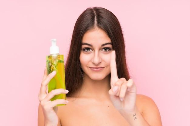 Jonge kaukasische vrouw die een vochtinbrengende crème met geïsoleerde aloë vera houdt die nummer één met vinger toont.