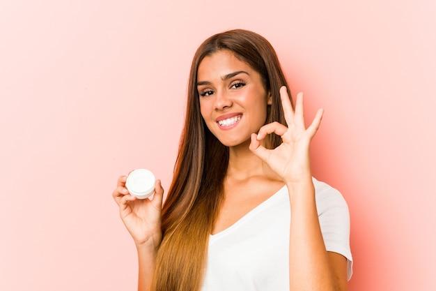 Jonge kaukasische vrouw die een vochtinbrengende crème vrolijk en zelfverzekerd houdt die ok gebaar toont.