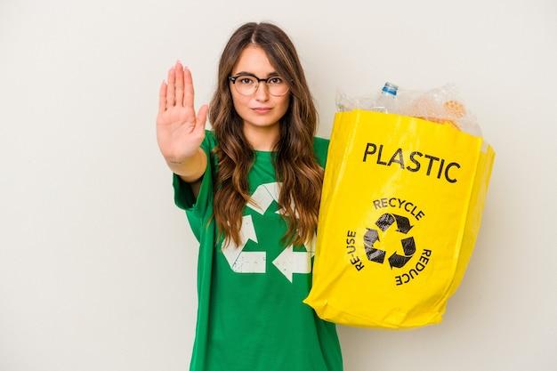 Jonge kaukasische vrouw die een volledige van plastic recycleert dat op witte achtergrond wordt geïsoleerdd die zich met uitgestrekte hand toont die stopbord toont, die u verhinderen.