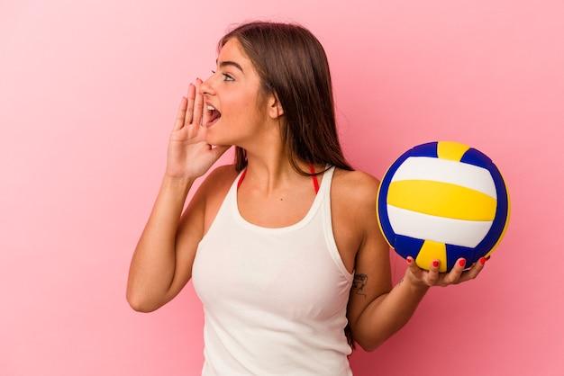 Jonge kaukasische vrouw die een volleybalbal houdt die op roze achtergrond wordt geïsoleerd die schreeuwt en palm dichtbij geopende mond houdt.