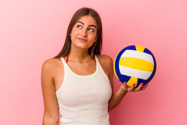 Jonge kaukasische vrouw die een volleybalbal houdt die op roze achtergrond wordt geïsoleerd en droomt van het bereiken van doelen en doeleinden