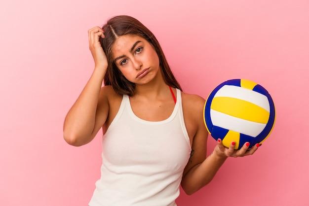Jonge kaukasische vrouw die een volleybalbal vasthoudt die op een roze achtergrond wordt geïsoleerd en geschokt is, herinnert zich een belangrijke vergadering.